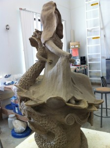 A work in progress, Sculpture of the goddess quan yin out of grey clay. this image: right side view