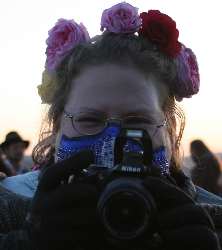 The author with a wreath of fresh roses on her head, and a camera in front of the lower half of her face, wearing a beaded mask over her nose and mouth.