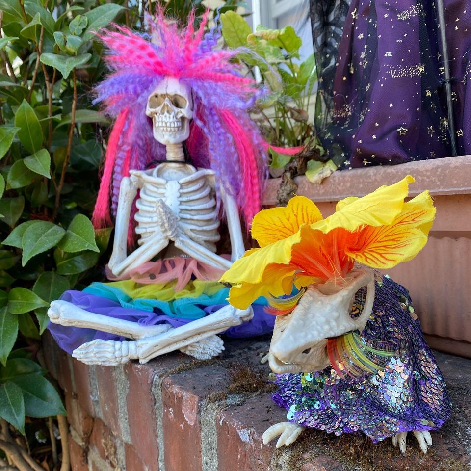 Decorated Halloween decorations: A skeleton praying figure dressed in pink and purple hair with a multicolored ruffled skirt sits next to a skeleton possum with a yellow hibiscus on its head, rainbow lashes, and a sequined drape.